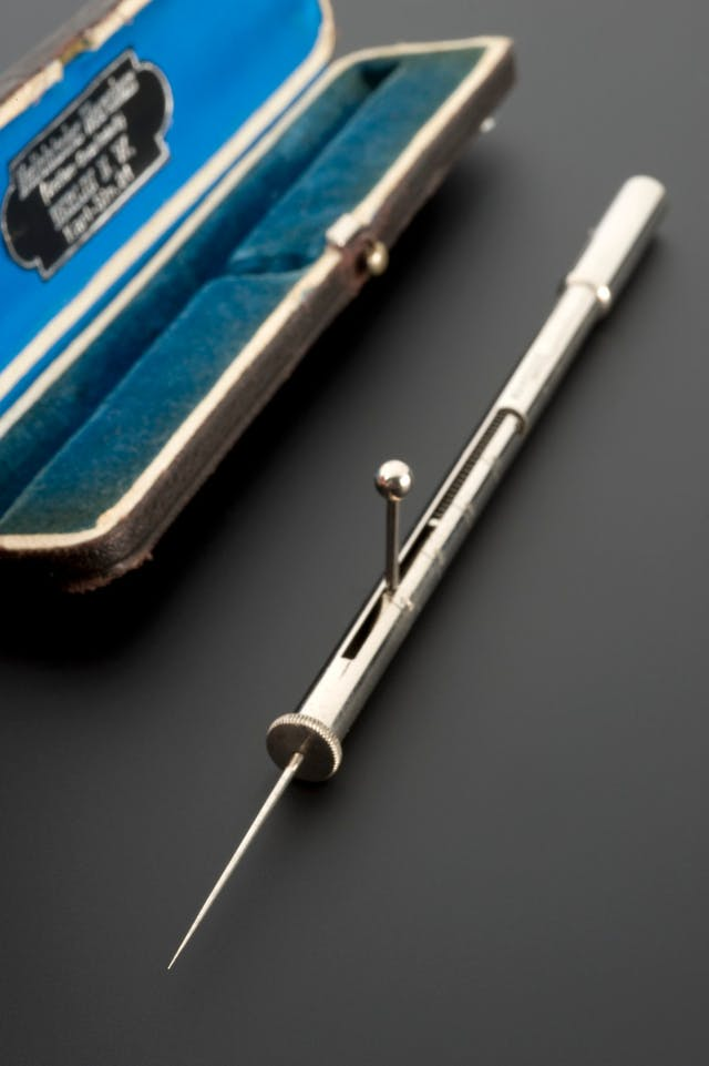 Photograph of an instrument case (in the background, lined with blue velvet) and a silver instrument called an algesimeter, which is a needle attached to a tube with a measure on the side to record the depth that a person is pricked before pain is expressed.