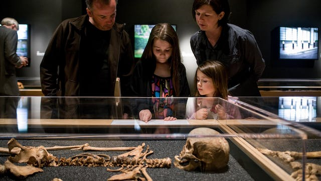 Photograph of a family looking at a display case showing one of the skeletons that formed part of the Skeletons: London's Buried Bones exhibition at Wellcome Collection.