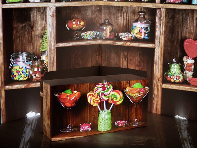 Photograph of the corner of a room showing the walls and a section of the wooden floor. On the floor is an arrangement of cardboard boxes. Onto the whole scene is projected an image of a sweet shop shelving with jars of sweets. The boxes have assumed the shape of the shelves and have jars of sweets projected onto their sides.