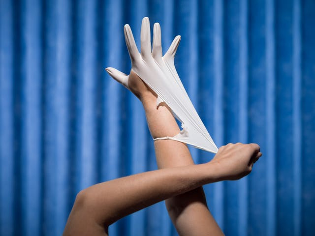 Photograph of a pair of hands, one hand is wearing a white latex glove, while the other stretches the cuff of the glove such that it is tearing. Photographed against a background of blue antibacterial clinical curtains.