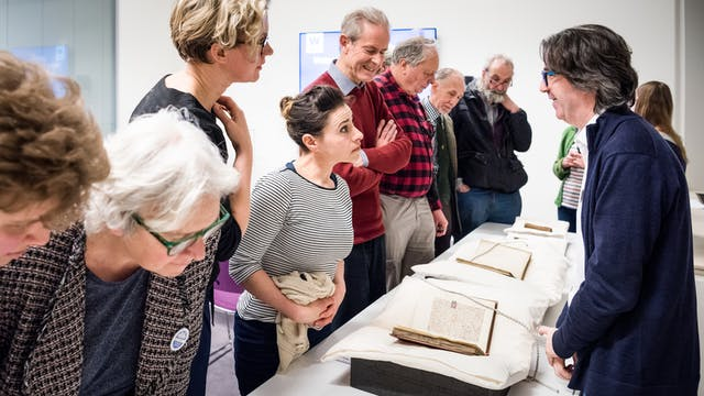 Photograph showing visitors examining archive material displayed on a table whilst talking to library staff.