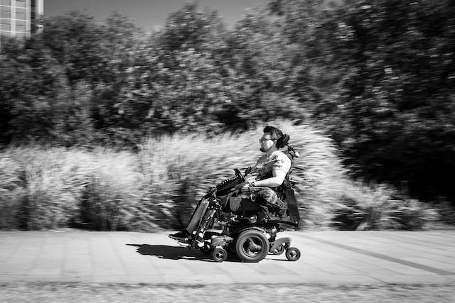 Black and white photograph of an individual racing along the pavement in their electric wheelchair.