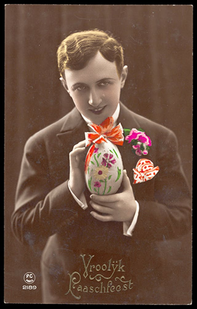 Young man holding decorated ester egg, with brightly coloured flowers in his lapel and a handkerchief in his breast pocket. The photograph is hand colourised.