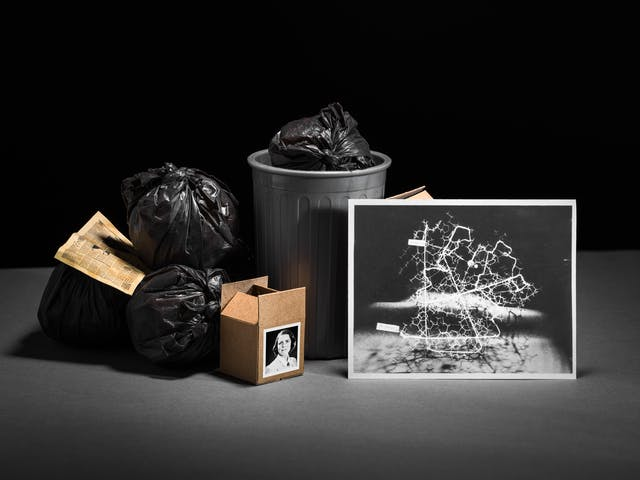 Photograph of a set-built scene made up of a grey card horizontal base against a black vertical background. In the centre of the image is a grey dustbin containing black bin bags. Surrounding the bin are more black bags and brown cardboard boxes. Leaning against one of the cardboard boxes is a black and white photographic print of a protein model.