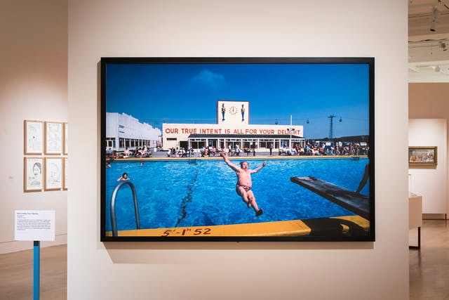 Photograph of an exhibition gallery space showing a section of light pink coloured wall, on which is hung a large colour photographic print. The print shows a sunny holiday camp scene with a large swimming pool in the foreground and a 1930 building in the background with the large words
