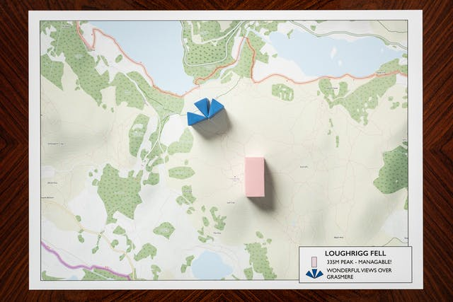 Photograph of a warm wood grained, polished tabletop from above. Resting on the table is a rectangular map showing roads, lakes, and the contours of hills. Resting on the map at strategic locations are two three dimensional shapes, a pink rectangle and blue fan shape made up of 3 triangles. To the bottom right of the map is a legend titled,