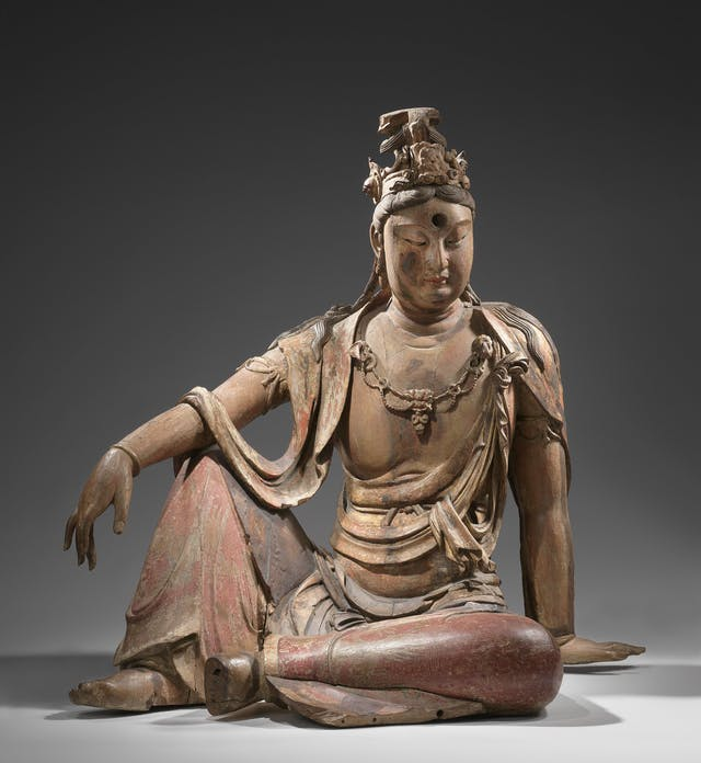 Figurine of seated figure, looking downward in contemplation.