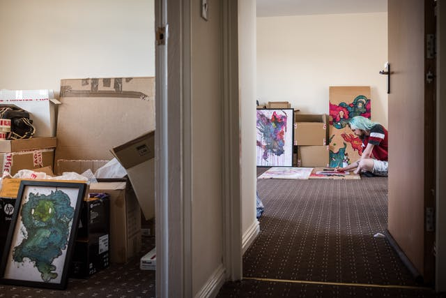 Photograph down the corridor of a flat showing unpacked boxes in one room and a man sitting on the floor creating a colour artwork in another.