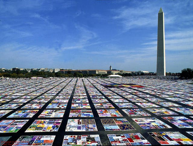 Picture of the AIDS quilt in front of the Washington Monument on a sunny day