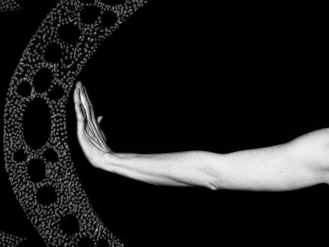 Artwork made up of a black and white photograph of a female figure from behind, from against a black background. Her left arm is held out straight to the side, her wrist and hand are held up indicating a stop action. To the left of her hand is part of a large ellipse made up of a layered texture of dots which forms a protective barrier against sharp tooth like forms approaching the barrier, also made up of layered textured dots.