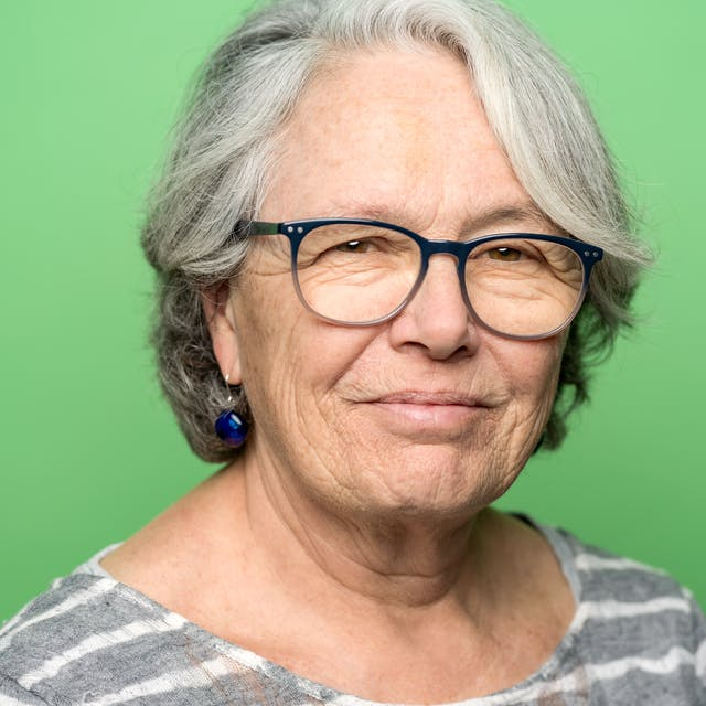 Portrait of Emily Engel head and shoulders on a green background