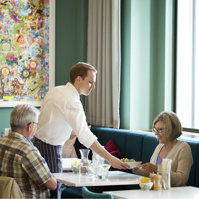 Three people sitting at tables in Wellcome Collection, while a server brings food to the table.