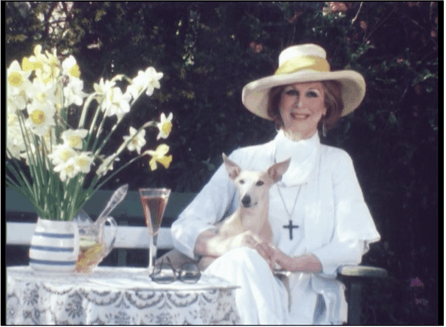 Film still of a woman wearing a yellow wide-brimmed sun hat and a white dress, with a dog on her lap. She is smiling and is next to a table with a vase daffodils on top.