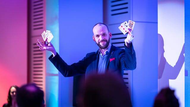 Photograph of a male magician holding up 2 playing cards in each hand, looking directly to camera. In the foreground are the backs of the heads of his audience. The magician is bathed in the pink and blue of the stage lighting.