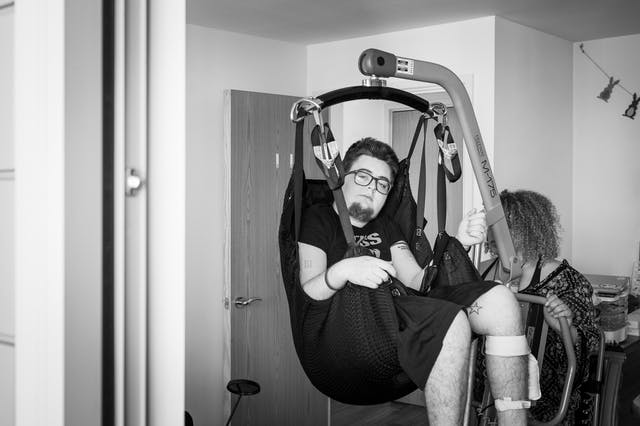 Black and white photograph of an individual at home in the process of hoisting themselves from their wheelchair.