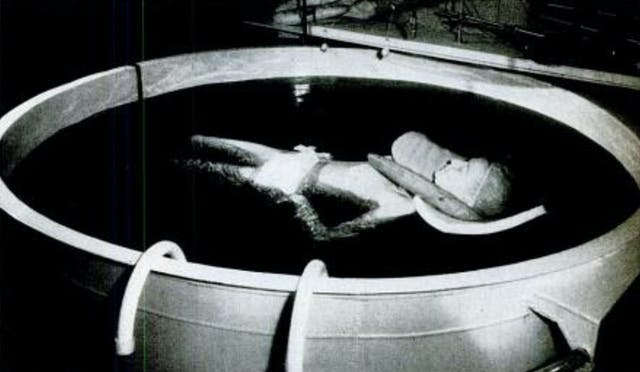 A woman floats in a tank of water on her back.