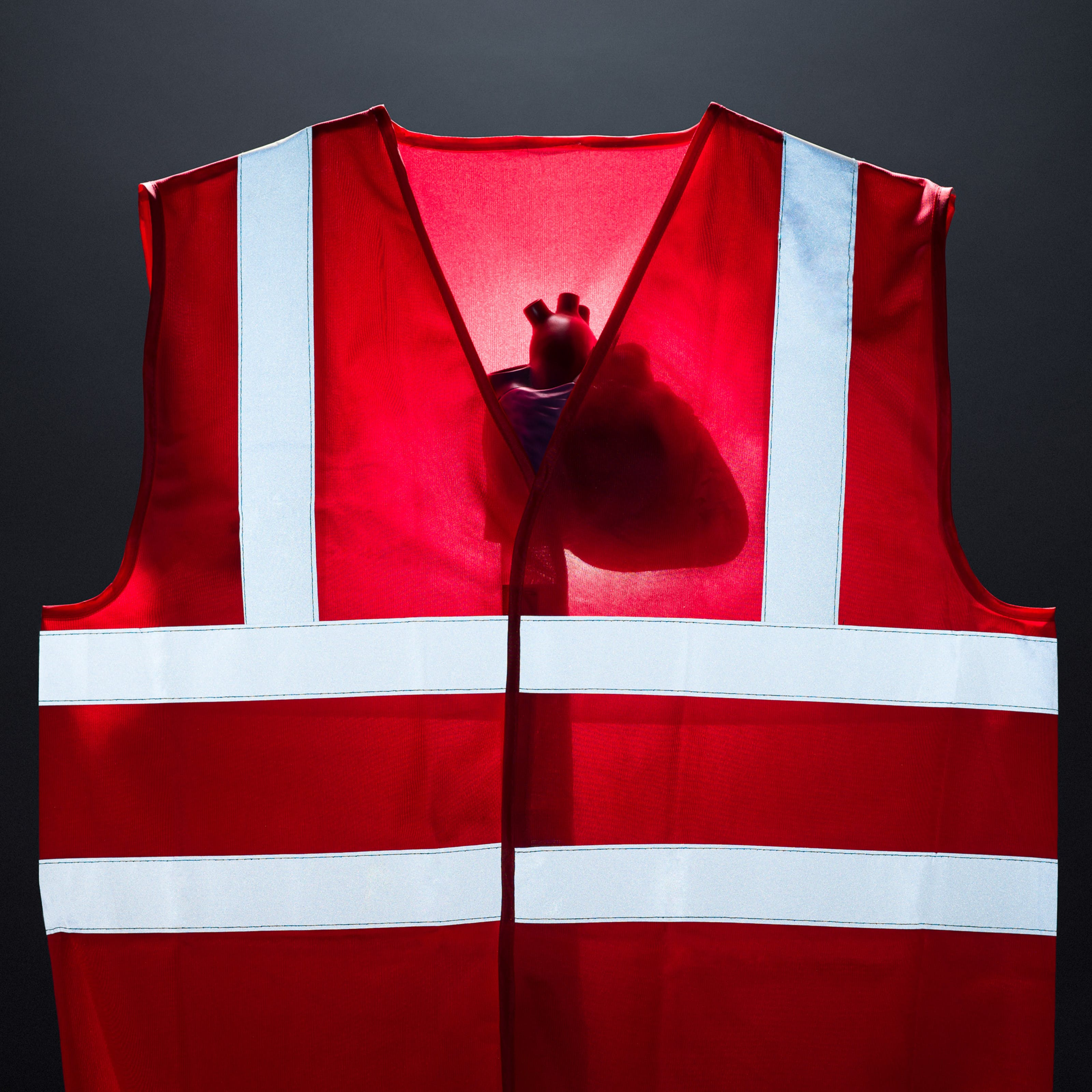 Photograph of a bright red high visibility vest against a dark grey background. The vest is lit from behind revealing the silhouette of a model of a human heart. The reflective strips on the front of the vest are bright with white light.