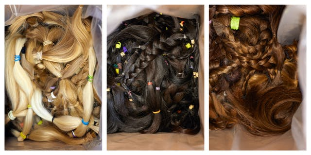 Photographic triptych. Each image is similar and shows a plastic lined cardboard box containing many hair donations, some plaited, some in a pony tail. In each image the open box is photographed from above and fills the frame. In the image on the right the box contains blonde hair, the box in the middle contains dark brown hair and the box on the right contains ginger hair.