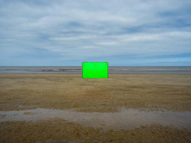 展示海滩景色的彩色风景照片。画面水平分为两半,上部是蓝天,云层覆盖,下部是沙滩,中间是一片薄薄的海洋和破碎的波浪。在图像的中心,有一个巨大的矩形摄影背景框竖立着。整个框架采用活力十足的绿色chroma key面料。在前景中,从左到右穿过沙子的是沙子中的一条薄水带。