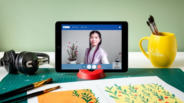 Portrait of Angela Chan who is on a video call on an iPad.  The iPad is propped up on a desk next to some art materials, paintbrushes, a half-finished painting of plants, and a pair of headphones.