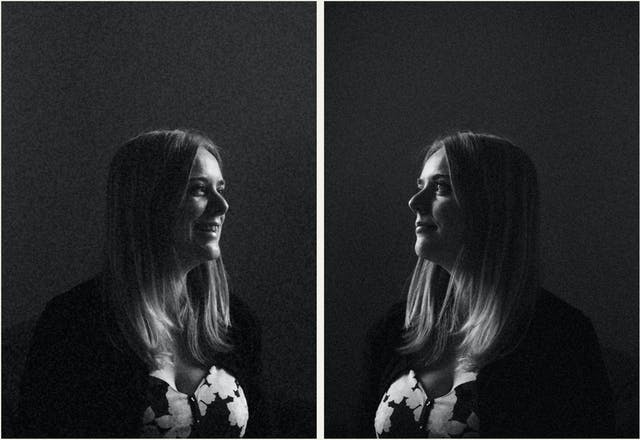 Photographic black and white diptych. The images both show the same young woman with blond hair, wearing a floral dress. In each image she is pictured in profile, looking towards herself in the other image, as if in a mirror. The image is very dark in tone, with just her profile picked out in the light. In the image on the left the woman is smiling. In the image on the right she has a more neutral expression.