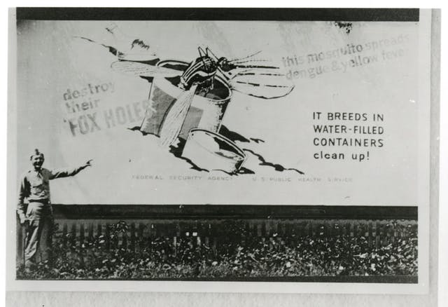Black and white photograph of a man in military uniform pointing to a billboard on which is the image of a mosquito breeding in a discarded can filled with water.