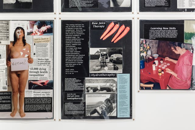 Photograph of a section of a gallery wall, showing several laminated sheets of black paper, overlaid with collages of text and imagery.