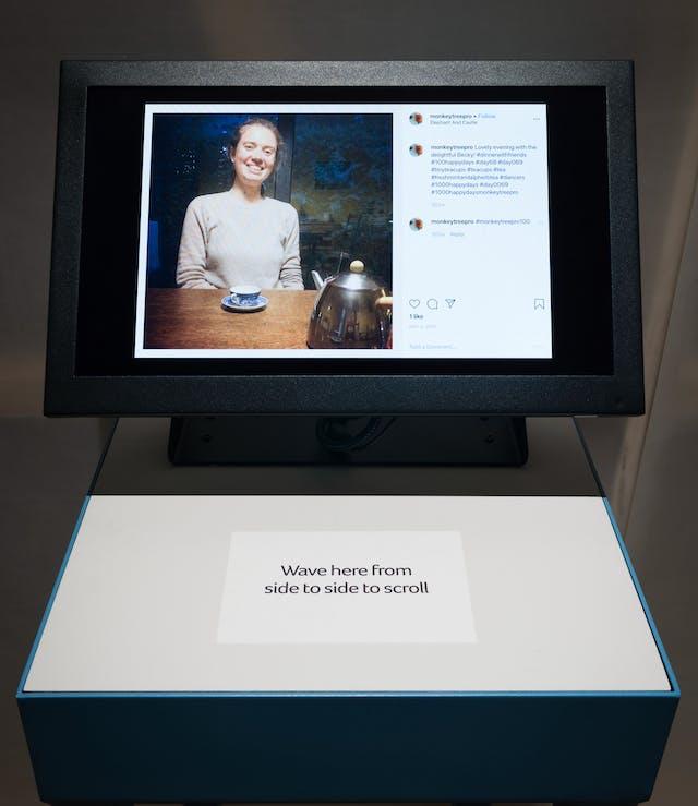 在展览馆的一张照片,显示一个安装在展览馆基座上的电脑屏幕。屏幕上是一个坐在木桌旁的年轻女子的形象,她面前放着一个蓝色的瓷器茶杯和茶托,还有一个闪闪发光的金属茶壶。她对着镜头微笑。图片的右侧是Instagram评论区的上下文图形,包括3条评论。屏幕前底座上的标签上写着:
