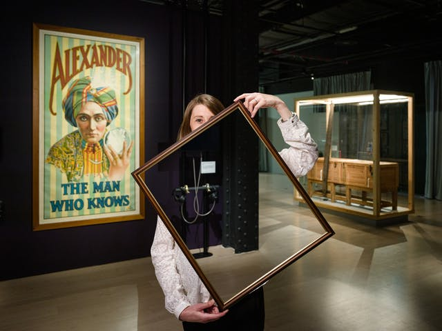 """Photograph of a woman in a dark gallery space holding a picture frame in front of her body and part of her face. Within the picture frame you can see straight through her, as if her body and half her face have disappeared. In the background you can see a large historical poster promoting the a magician called """"Alexander, the man who knows"""" and a sawing in half box."""