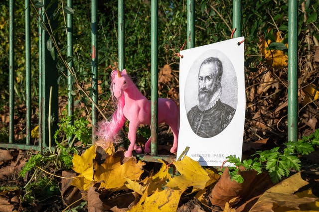 Photograph of a line of green metal railings, fairly closeup, in a park or garden. The railings are surrounded by autumnal leaves on the ground and bush foliage behind. Tied to the railings is a paper poster with a black and white print of a bearded man wearing a ruff, from the 16th century. To the left of the poster a pink plastic unicorn figurine is appearing through the railings.