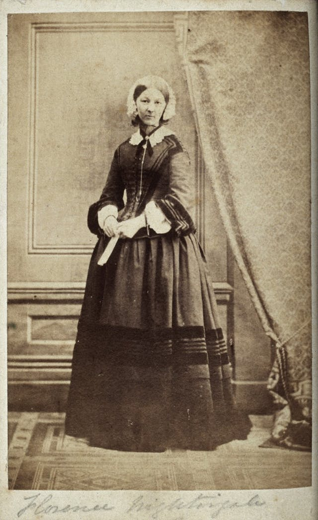A black and white portrait of Florence Nightingale, wearing a full length dress and bonnet.