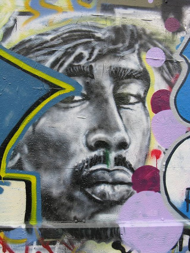 Photo of graffiti depicting the face of rapper 2Pac with colourful border