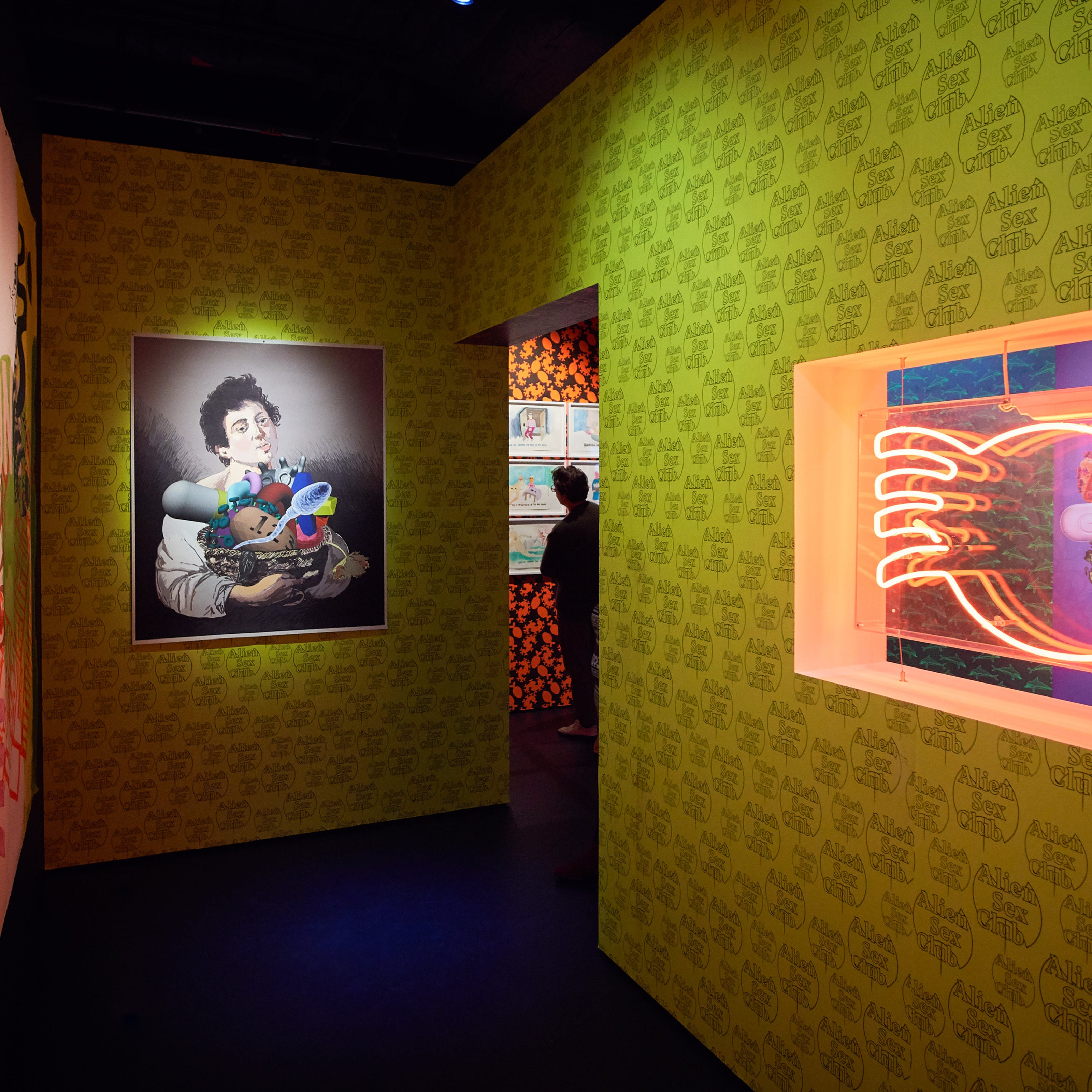 Photograph of a visitor in the distance looking at framed artworks on the wall. In the foreground is colourful patterned wallpaper, a work of art and a red neon exhibit.