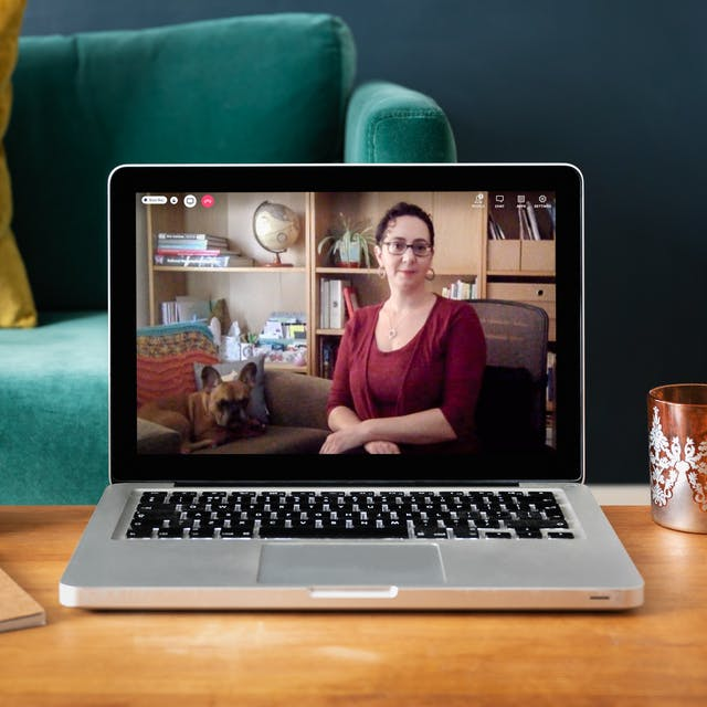 A photograph of a laptop on a wooden coffee table in a colourful blue living room. On the laptop screen is a live online event with Anna Feigenbaum who is sitting in a chair with tied-up curly brown hair. Next to her in an armchair is her French Bulldog.