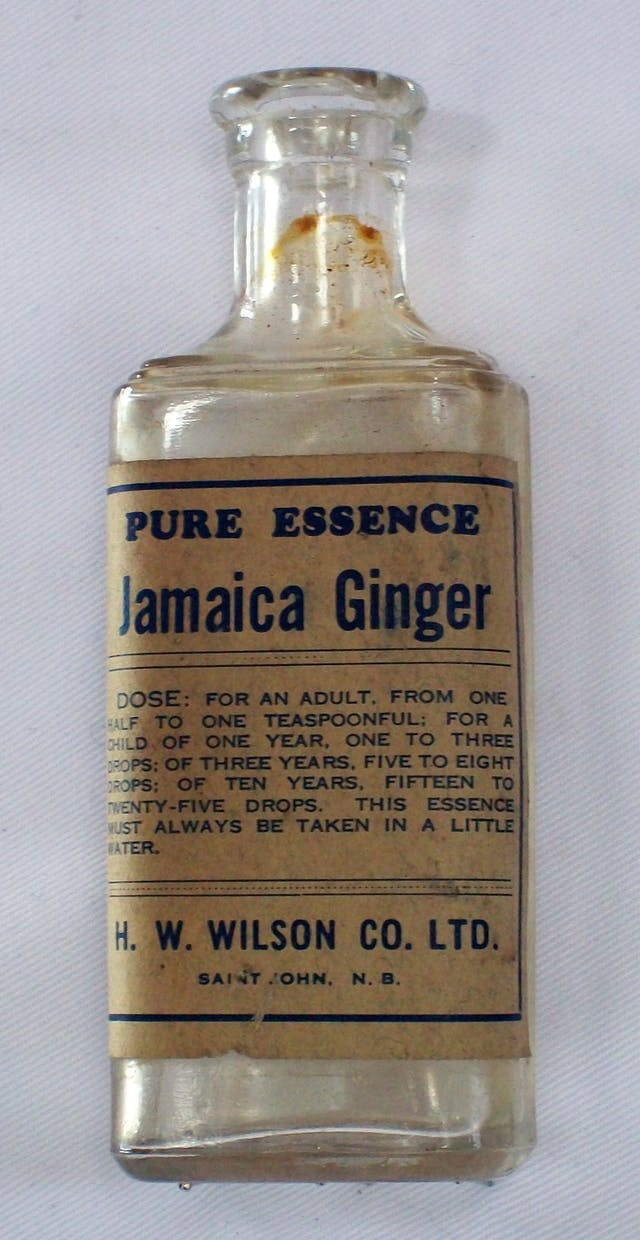 A glass bottle with browned-paper label saying: Pure essence Jamaica Ginger. Recommended dose and manufacturer