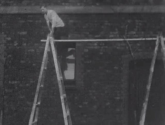 Black and white still showing a man with his hand bandaged up tightly, perched at the top of a ladder about to climb onto a plank balanced between his ladder and another.