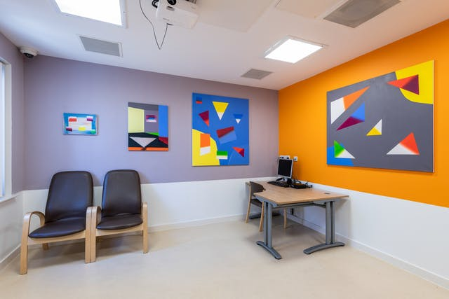 A photograph showing a room containing a desk, computer and two chairs with their backs to the wall. On a lilac painted wall there are three rectangular paintings on canvas boards, of three different sizes, small, medium and large running from left to right. Each painting appears as a collage made up of triangles and quadrilaterals of a various colours floating on different blue backgrounds. The adjacent wall is painted bright orange on which another larger painting, similar in design, hangs. This time the shapes float on a solid grey background.