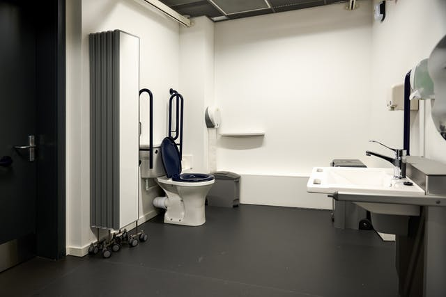 Photograph of the interior of a modern looking accessible toilet, showing the toilet, a screen on wheels, basin and sanitary bins.