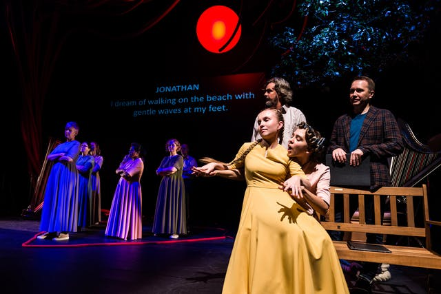 """Photograph of a theatre stage. In the foreground and lit by stage light, a female actor wearing a mustard yellow formal costume is sitting on the knee of another actor. The actor in yellow is resting her arms and palms over the arms and hands of her fellow actor, who is speaking over her shoulder. In the background a number of other actors standing in a triangular formation within the confines of a red rope laying on the floor. On the projection in the far background, blue text reads """"Jonathan: I dream of walking on the beach with gentle waves at my feet."""""""