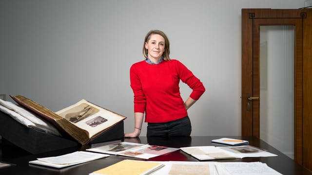 Katherine Hubbard standing behind a table with archive materials on it