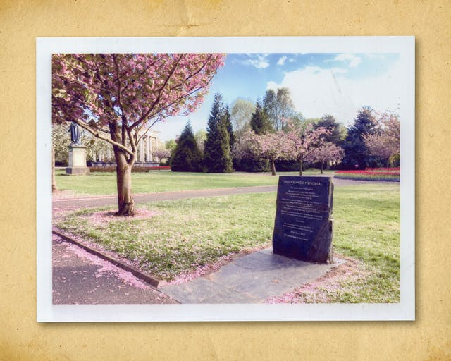 Photograph of a colour photographic inkjet print, resting on a brown paper textured background. The print shows a memorial stone in a parkland. It is surrounded by grass and a tree in blossom, whose petals have begun to fall and cover the ground. In the background are trees, a statue and a columned building. The title of the memorial can just be read, showing the words,