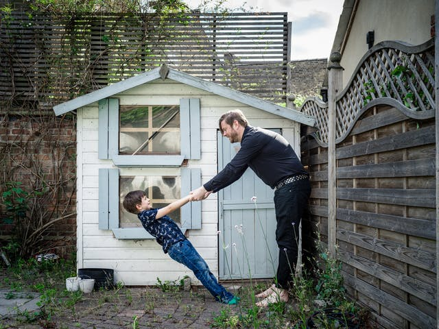 Photograph of a man and his young son in their back garden in front of a Wendy house. They are holding hands and the young son is leaning back at an extreme angle, held up only by his father.