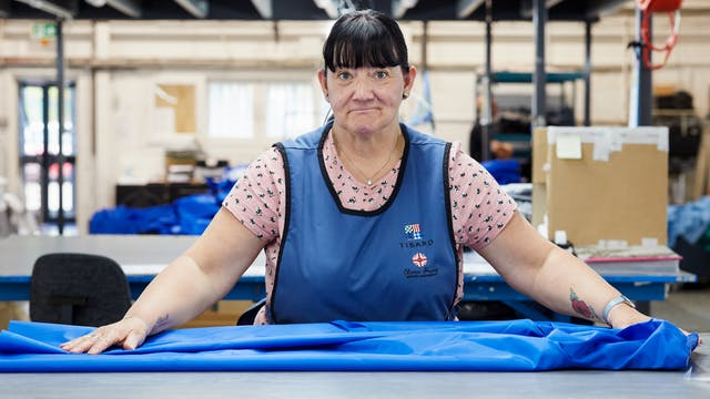 Photograph of a woman in a textile factory wearing  a blue tunic. She is look straight to camera with her hands outstretched to either side resting on a blue medical garment. In the background are cardboard boxes and other workstations.