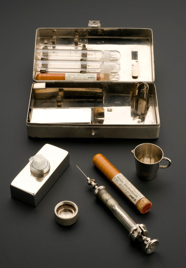 Rectangular metal box containing empty phials. in front of the case, its other contents are laid out: a bottle-shaped container holding cotton wool, a metal syringe with glass body, a tube of quinine bihydrochloride and a small metal jug.