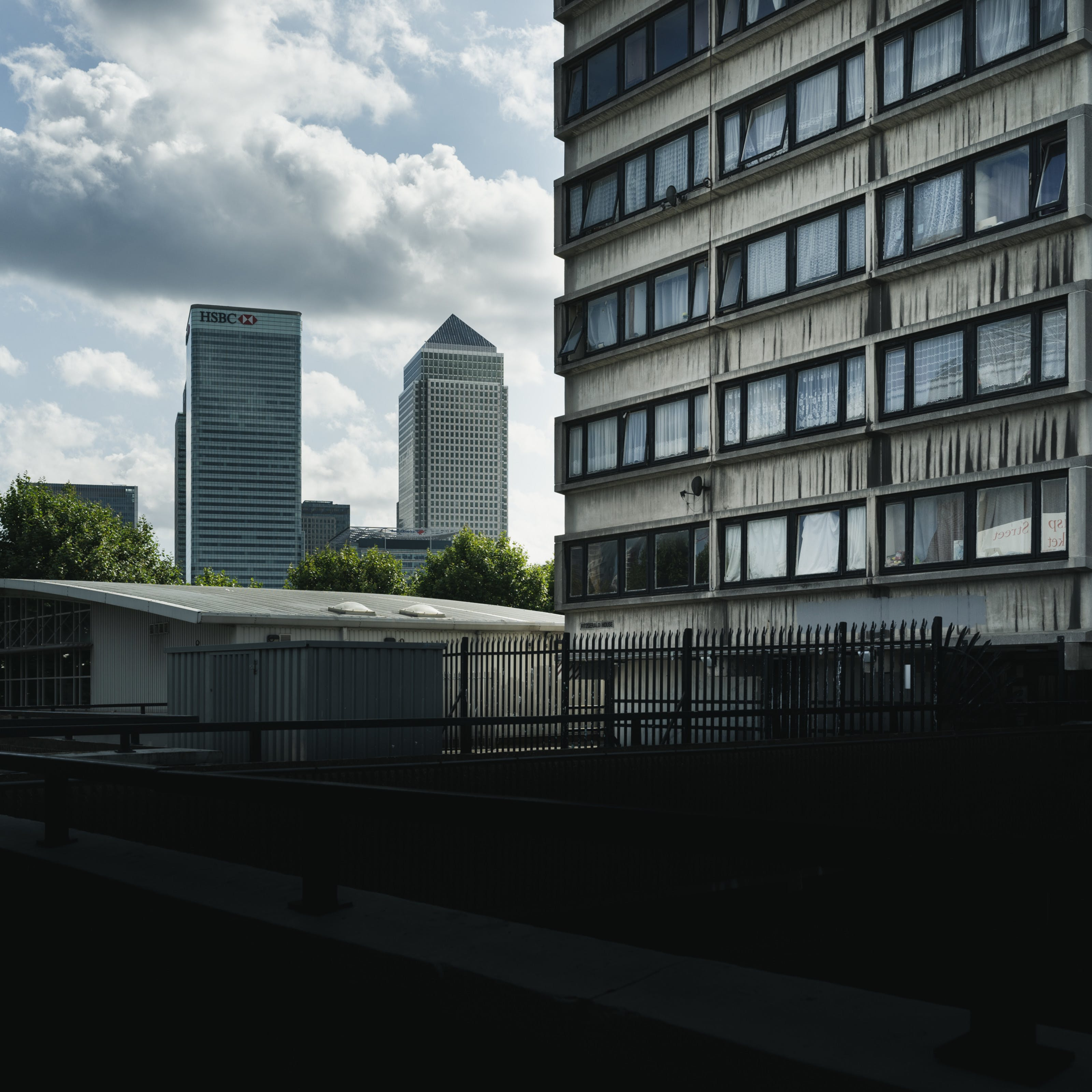 Photograph of a view towards Canary Wharf with a section of a council high rise block of flats in the foreground.