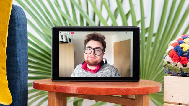 """Photograph of a tablet standing on a wooden stool. On the tablet screen is a photographic portrait of Jamie Hale, wearing glasses, a grey sweater with a pink collar showing. Also, on the screen are video call icons """"People"""", """"Chat"""" and a red telephone icon. There are green decorative palm leaves displayed in the background behind the tablet which is next to a colourful folded blanket and the edge of a blue sofa with a yellow cushion."""