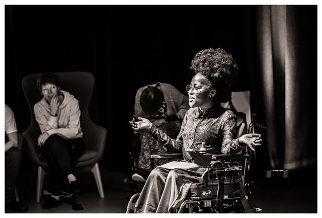 Black and white photograph with a warm tone. The image shows a young woman seated in a wheelchair against a black curtain and lit by a spotlight. She is performing to an audience which can be seen seated to her right int he background. She has been captured