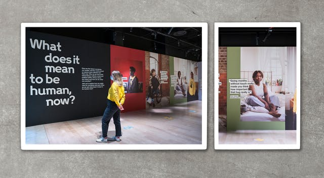 Photograph of two photographic colour prints resting on a grey, concrete textured surface, from directly above. The prints are slightly raise off the surface, casting a small shadow. The prints show a gallery installation. The image on the left shows an individual in a yellow top and dark trousers, wearing a face covering, who is reading an information panel on the gallery wall. In front of them are large title graphics with the words,