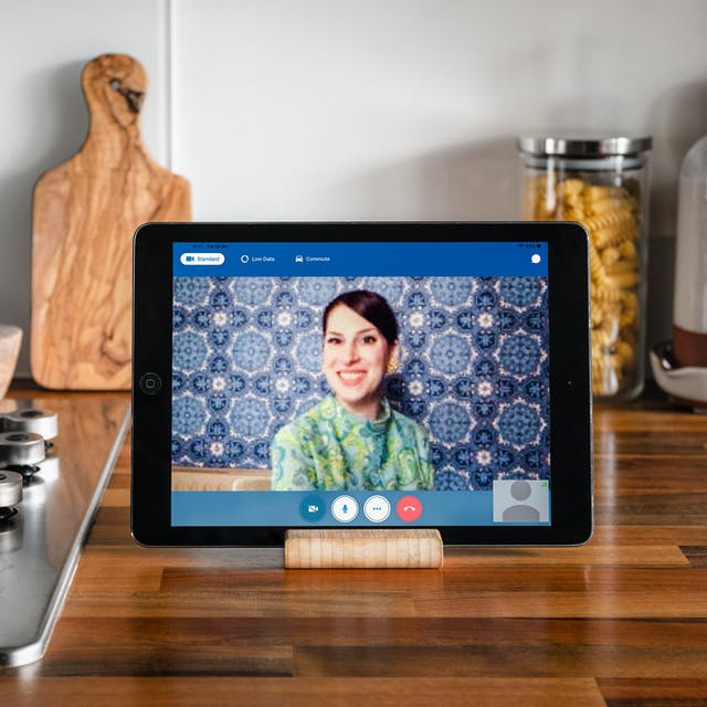 Jessica Borge appearing on a video call on a tablet device. Her brown hair is tied up, she is wearing gold earrings and a bright green patterned top, behind her is blue patterned wallpaper.  The tablet is sitting on a kitchen counter next to a gas hob with wooden chopping boards in the background and a glass tub containing pasta.