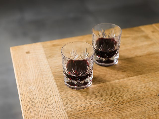 A photograph of a corner of a wooden table with two small tumbler-style glasses. The glasses contain red wine, and are filled below halfway. The glasses have detailed ridges on the outside in palmleaf-like patterns.